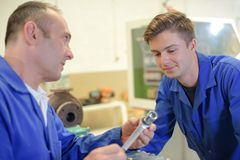 Man showing socket wrench to trainee. Socket royalty free stock photos