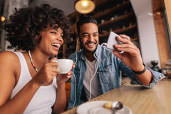 Man showing something on cellphone to his girlfriend. Young men showing something on cellphone to his girlfriend at cafe. Happy young couple sitting at coffee Stock Photo