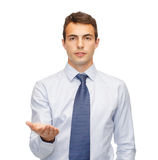 Man showing something on the palm of his hand. Business and office, advertising, people concept - friendly young buisnessman showing something on the palm of his Royalty Free Stock Images