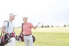Man showing something to friend at golf course against clear sky Royalty Free Stock Photo