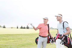 Man showing something to friend at golf course against clear sky Stock Image