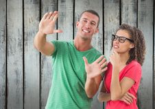 A man showing something to a girl in front of wood wall. Digital composite of A men showing something to a girl in front of wood wall stock images