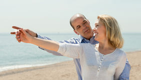 Man showing something to his wife on the beach. Smiling elderly men showing something to his wife on the beach Stock Photos