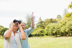 Man showing something to his wife with binoculars Stock Photography