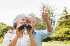 Man showing something to his wife holding binoculars Royalty Free Stock Photo