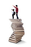 Man showing something to little child. Businessman on a pile of books and showing something to little child Royalty Free Stock Images