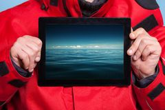 Man showing stormy sea on tablet. Travel. Stock Image