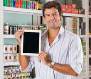 Man Showing Tablet In Grocery Store. Portrait of happy mid adult man showing digital tablet in grocery store royalty free stock image