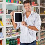 Man Showing Tablet In Supermarket. Portrait of happy mid adult man showing digital tablet in supermarket Stock Photography