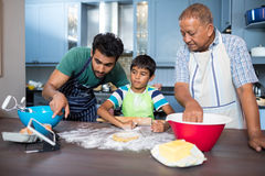 Man showing tablet to son while preparing food. With grandfather in kitchen at home Royalty Free Stock Image