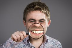 Man showing teeth. Man with magnifying glass showing teeth Stock Images
