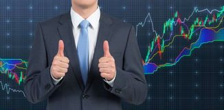Man  showing  thumb up. Businessman showing thumb up on forex chart background Stock Images