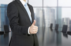 Man showing thumb up. Businessman standing in office and showing thumb up Stock Photos