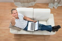 Man Showing Thumb Up While Working On Laptop. Young Happy Man Showing Thumb Up While Working On Laptop At Home stock photos