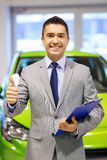 Man showing thumbs up at auto show or car salon Stock Images