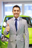 Man showing thumbs up at auto show or car salon Stock Photos