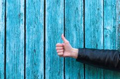 Thumbs up. Man is showing a thumbs up on a blue wooden fence background with copy space stock images
