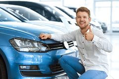 Man showing thumbs up at the car salon. Plus one driver on the road! Happy young man showing thumbs up posing near his newly bought car at the dealership royalty free stock photo