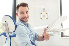 Man showing thumbs up at the dental clinic. Handsome man showing thumbs up and smiling sitting at the dental chair. Professional dental clinic, healthy teeth stock image