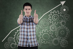 Man showing thumbs up with a gear background Stock Photos
