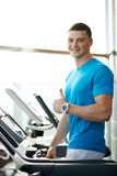 Man showing thumbs up near the treadmill Royalty Free Stock Photography