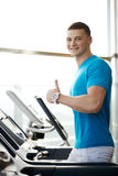 Man showing thumbs up near the treadmill Stock Photo