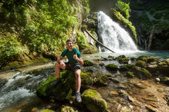 Man showing thumbs up sign outdoor near a waterfall Stock Image