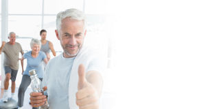 Man showing thumbs up sign with people exercising in background Royalty Free Stock Photos
