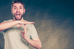 Man showing time out gesture sign and screaming. Royalty Free Stock Images