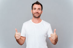 Man showing two thumbs up and looking at camera Stock Photos