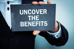 Man showing Uncover the benefits word. Man showing Uncover the benefits word on cardboard Stock Image