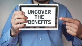 Man showing Uncover the benefits word. Man showing Uncover the benefits word on tablet screen Royalty Free Stock Image