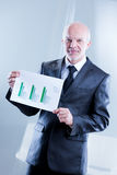 Man showing up some graphs with shy smile Stock Images