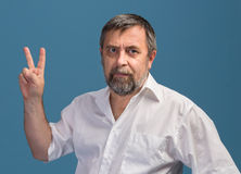 Man in  showing victory sign Royalty Free Stock Image