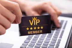 Man Showing VIP Member Card While Using Laptop. Man`s Hand Showing VIP Member Car While Typing On Laptop Keypad stock images