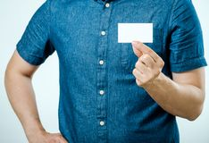 Man showing white blank business card isolated. Focus on card Stock Image