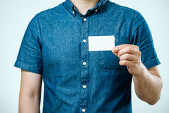 Man showing white blank business card isolated. Focus on card Stock Photography