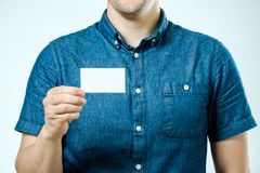 Man showing white blank business card isolated. Focus on card Stock Images