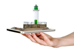 Man is showing white lighthouse with green details through mobile phone Stock Photos
