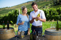 Man showing wine bottle to woman while standing by table Royalty Free Stock Images