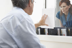 Man Showing Woman Paper In Office Stock Photography