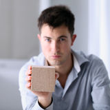 Man showing a wooden cube Stock Image