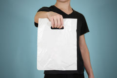 Man shows blank plastic bag mock up isolated. Empty white polyethylene package mockup. Consumer pack ready for logo design or ide. Ntity presentation. Commercial stock images