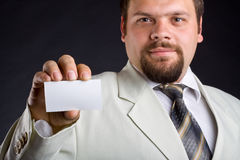 A man shows a business card. Focus on hand. Royalty Free Stock Photography