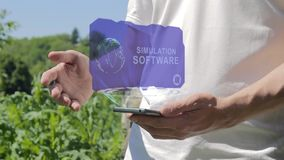 Man shows concept hologram simulation software on his phone. Person in white t-shirt with future technology holographic screen and green nature background