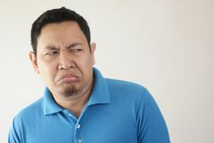 Man Shows Disgusted or Displeased Expression. Portrait of young Asian man shows disgusted or displeased expression rejection person adult face emotion reaction stock image