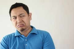 Man Shows Disgusted or Displeased Expression. Portrait of young Asian man shows disgusted or displeased expression rejection person adult face emotion reaction royalty free stock photo
