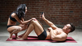 Man shows girl his phone while lying on a carpet Stock Photo