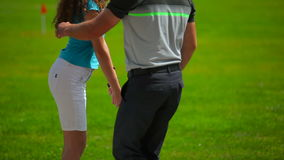 Man shows girl how to hold a club in hands in golf stock footage
