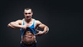 A man shows his abdominal muscles Royalty Free Stock Image